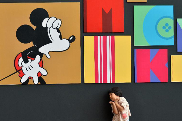 A child plays in front of a wall presenting Disney figure Mickey at the Walt Disney 90th Anniversary Exhibition in Indigo Department Store in Beijing, Sept 6, 2014.[Photo: Xinhua]