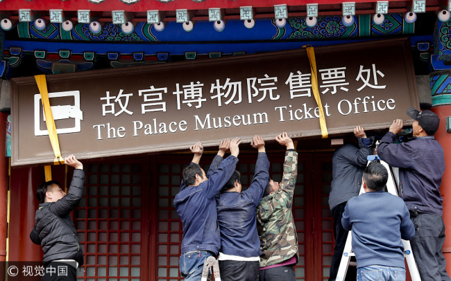 Workers take down a sign at the Palace Museum's ticket office in Beijing on Tuesday. [Photo: VCG]