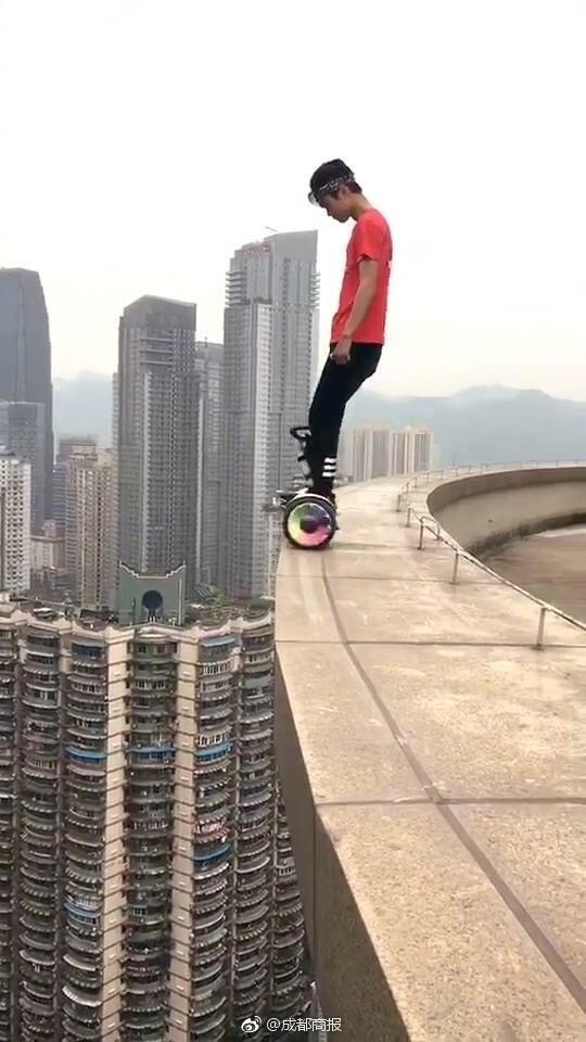 Wu rides a balance bike on the roof edge of a high building. [Photo: sina.cn]