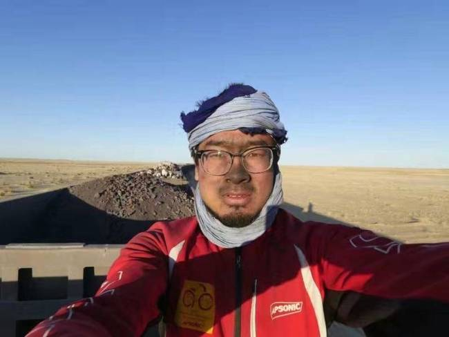 Yuan Jianglei poses for a photo on his 16,000-kilometer ride to come back to his hometown from Africa's Benin. [Photo: Beijing Youth Daily]