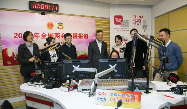 Wang Lian(4th, left), chief engineer of China Radio International(CRI), inspects China Plus's live broadcast room in Beijing, on March 4, 2018. [Photo: China Plus]