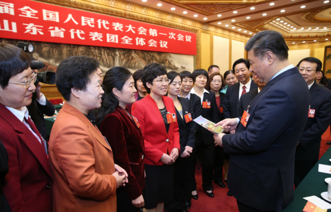 President Xi Jinping looks at a photo showing football training for female high school students while at a panel discussion with deputies from Shandong Province who are in Beijing for the 13th National People's Congress (NPC). [Photo: Xinhua/Yao Dawei]