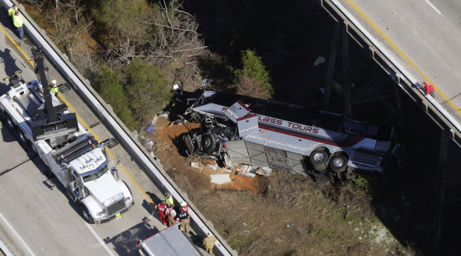 Rescue crews work at the scene of a deadly charter bus crash on Tuesday, March 13, 2018, in Loxley, Ala. The bus carrying Texas high school band members home from Disney World plunged into a ravine before dawn Tuesday. [Photo: AP/Dan Anderson]