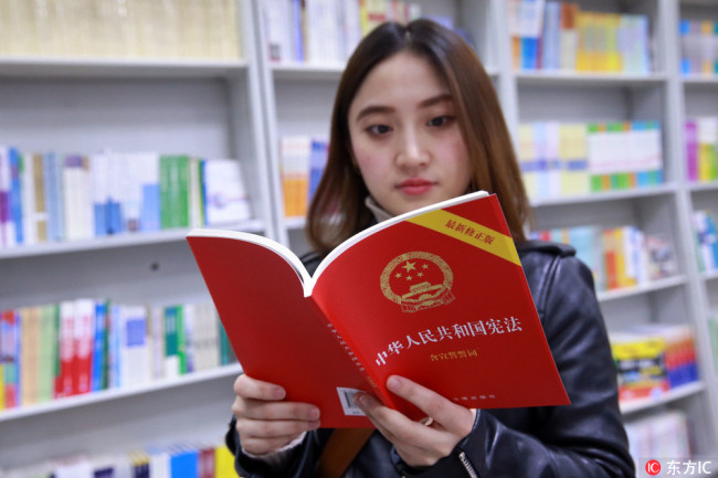 A reader reads China's amended Constitution in Wangfujing Bookstore in Beijing on March 13, 2018. [Photo: IC]