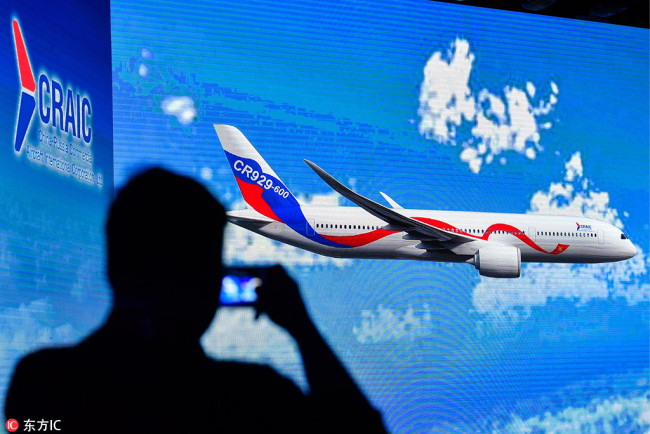 A staff member takes picture of a video screen showing the CR929 wide-body long-range passenger aircraft during a ceremony at the headquarters of the Commercial Aircraft Corporation of China (COMAC) in Shanghai on September 29, 2017. [Photo: IC]