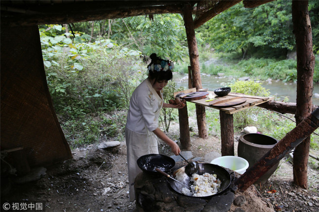 Zhang uses a wood-burning stove to make rice with potatoes, creating a taste of her childhood. [Photo/VCG]