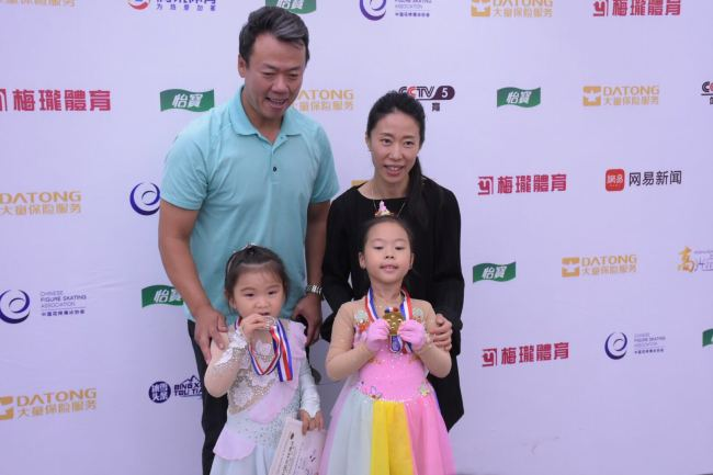 China's former Olympian medalist pair Zhao Hongbo[L] and Shenxue [R]take photos with their five-year-old daughter Zhao Xuer at Tus ice and snow sports center in Beijing on July 1, 2018. [Photo: China Plus/ Wangbo Malonsports ]