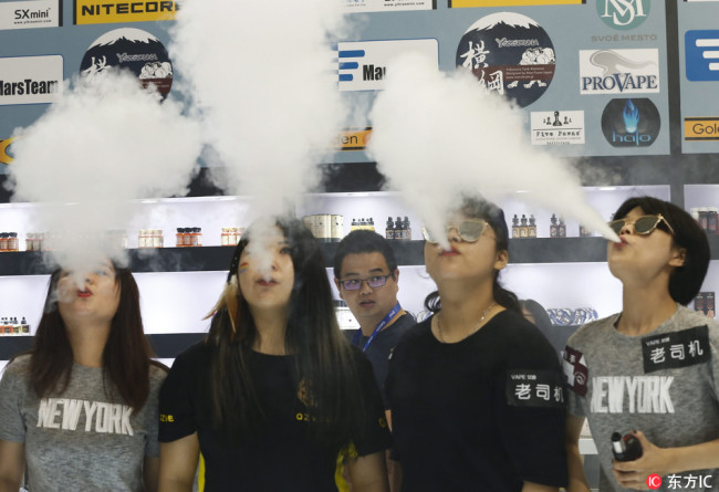 People use e-cigarettes at an exhibition center in Beijing on July 29, 2016. [File photo: IC]