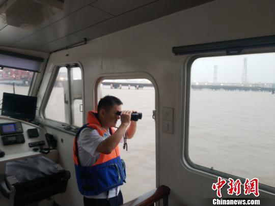 A staff member of the maritime safety authority in Ningbo, east China's Zhejiang province inspects the Beilun harbor, August 12, 2018. [Photo: Chinanews.com]