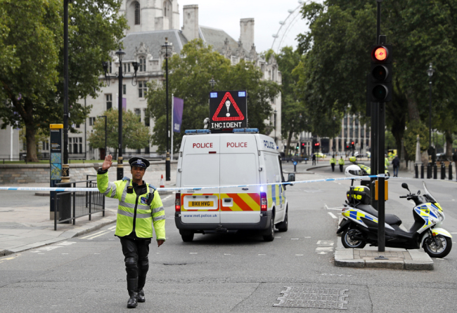 A police officer gestures as he stands in a road in central London, after a car crashed into security barriers outside the Houses of Parliament, in London, Tuesday, Aug. 14, 2018. [Photo: AP/Alastair Grant]