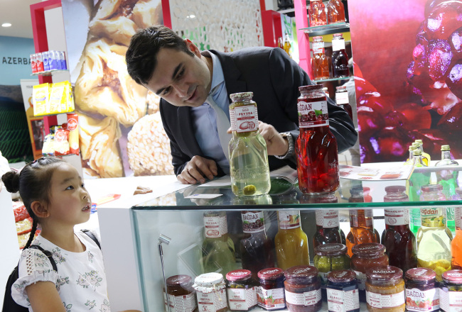 An Azerbaijani exhibitor introduces his company's compotes, a unique local food, to a visiting child during the 6th China-Eurasia Expo in Urumqi, Xinjiang Uygur Autonomous Region on Thursday, August 30, 2018. [Photo: China Plus / Sang Yarong]