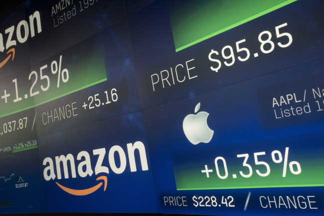 Amazon and Apple stock prices are shown on an electronic screen at the Nasdaq MarketSite, Tuesday, Sept. 4, 2018, in New York. Amazon became the second publicly traded company to be worth $1 trillion, hot on the heels of Apple. [Photo: AP/Mark Lennihan]