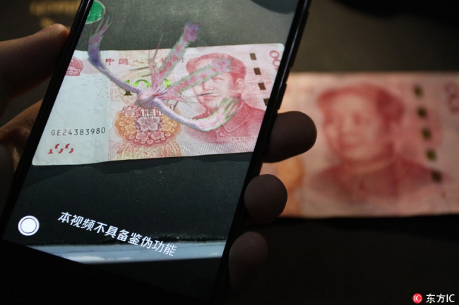An animation of a phoenix appears above a 100 yuan at the launch of a new QQ app feature that aims to teach users how to spot counterfeit notes, seen here on Tuesday, September 11, 2018. [Photo: IC]