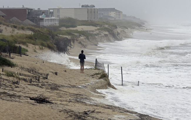 Heavy surf crashes the dunes at high tide in Nags Head, N.C., Thursday, Sept. 13, 2018 as Hurricane Florence approaches the east coast. [File photo: AP/Gerry Broome]
