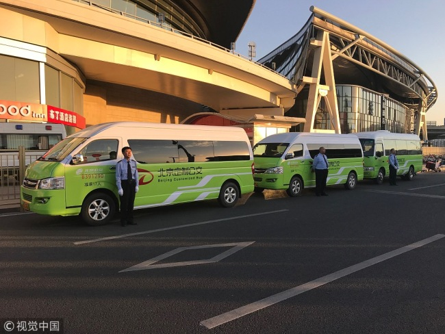 Drivers stand beside minibuses to be used for a new online bus-pooling service at the Beijing South Railway Station, September 22, 2018. [Photo: VCG]