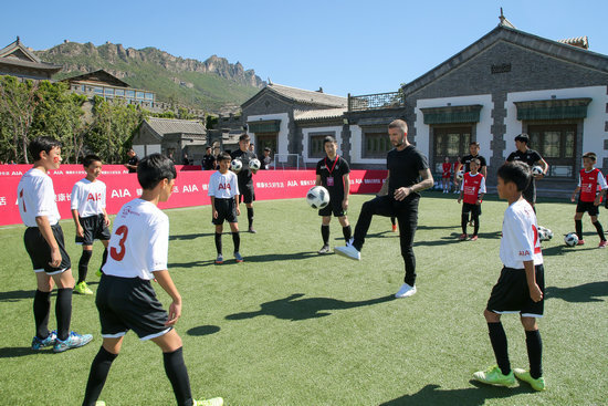 British football star David Beckham plays the football with children on Sept. 23. [Photo: people.com.cn]
