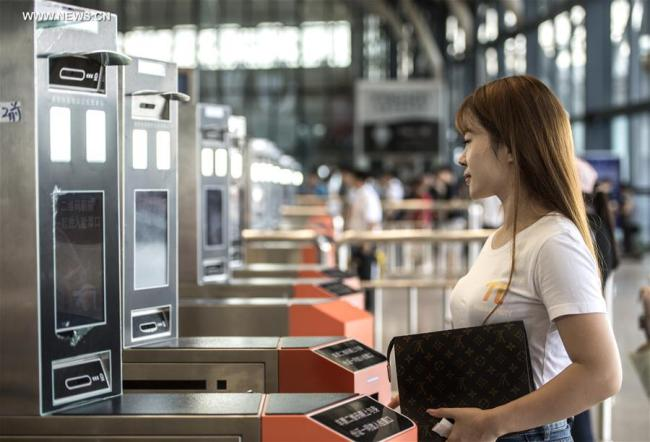 A passenger uses her identification card at a facial recognition scanner as she prepares to board a train at Wuhan Railway Station in Hubei Province on August 22, 2017. [Photo: Xinhua]
