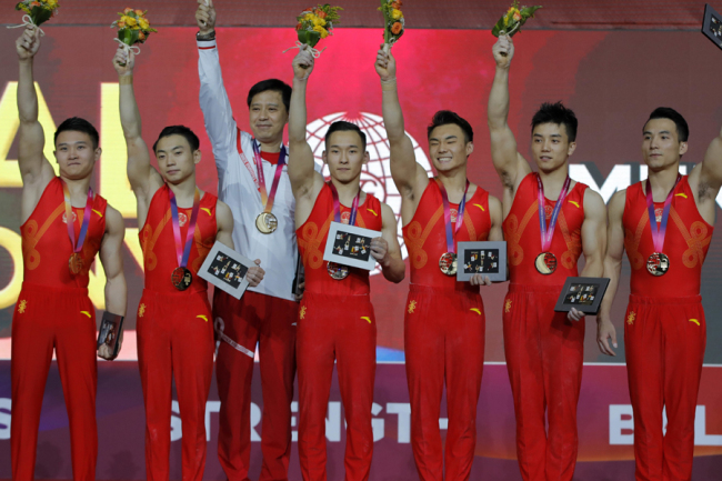 World champion team China with Deng Shudi, Lin Chaopan, Sun Wei, Xiao Ruoteng, Zou Jingyuan and their coach pose with their gold medals during the men's team final of the Gymnastics World Chamionships at the Aspire Dome in Doha, Qatar, Monday, Oct. 29, 2018. [Photo: AP]