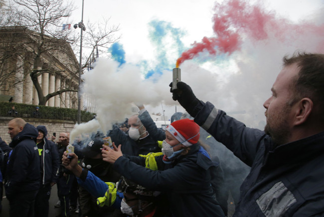 Ambulance workers hold flares outside the National Assembly in Paris, Monday, Dec. 3, 2018. [Photo: AP /Michel Euler]
