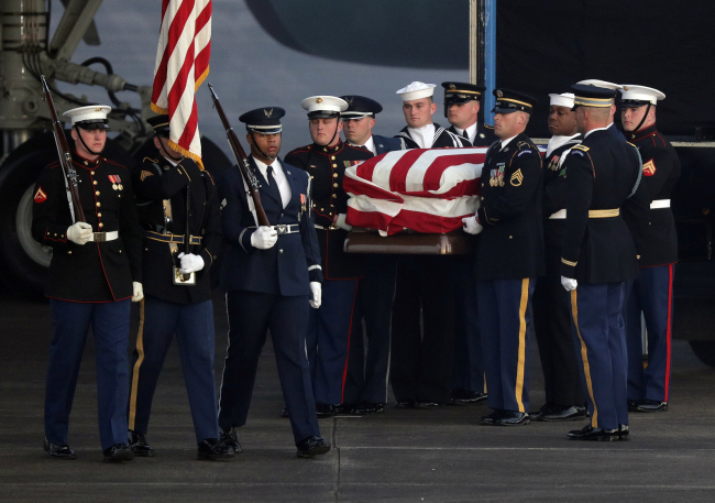 The flag-draped casket of former President George H.W. Bush is carried by a joint services military honor guard Wednesday, Dec. 5, 2018, at Ellington Field in Houston. [Photo: AP]