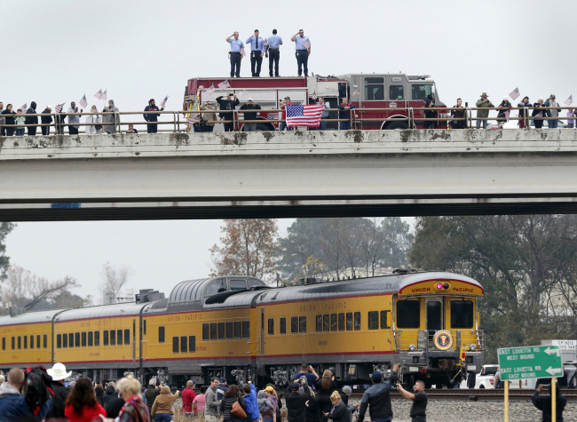 Firefighters stand on their truck and salute along with other attendants on an overpass as the train carrying the body of former president George H.W. Bush travels past on the way to Bush's final internment Thursday, Dec. 6, 2018, in Spring, Texas. [Photo: AP/Michael Wyke]