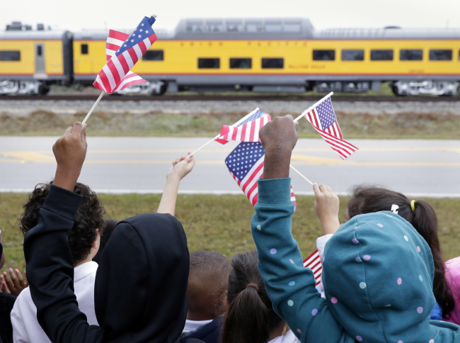 Students from Salyer Elementary School wave flags as the train carrying the body of former president George H.W. Bush travels past their school on the way to Bush's final internment Thursday, Dec. 6, 2018, in Spring, Texas. [Photo: AP/Michael Wyke]