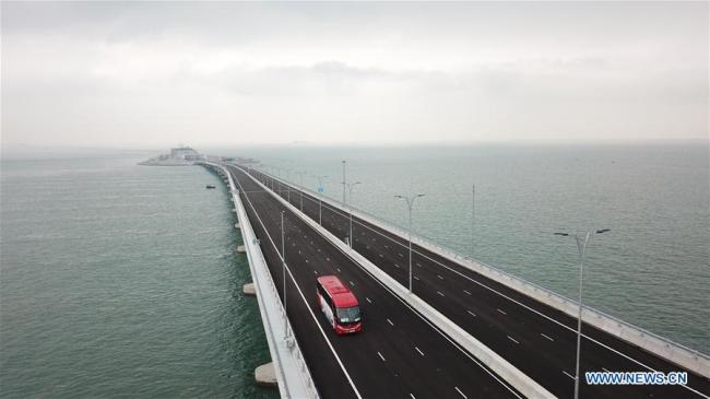 Aerial photo taken on Oct. 24, 2018 shows a car running on the Hong Kong-Zhuhai-Macao Bridge. The Hong Kong-Zhuhai-Macao bridge, the world''s longest cross-sea bridge, opened to public traffic Wednesday. [Photo: Xinhua/Lui Siu Wai]