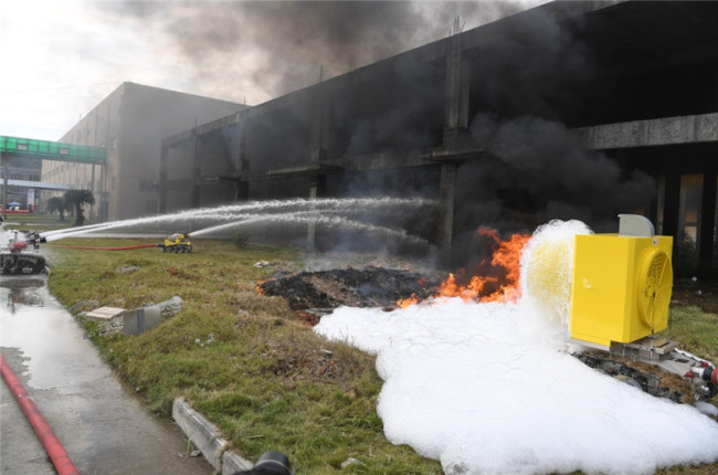 Firefighting robots spray water and foam during a drill at a factory in Ningde, Fujian Province on Wednesday, December 12, 2018. [Photo: Xinhua]