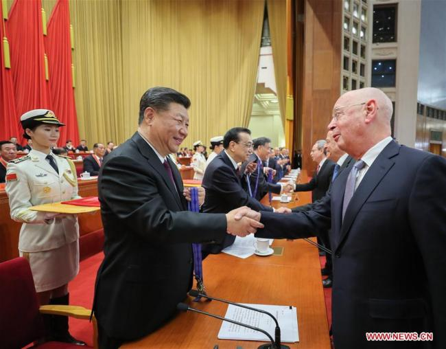 Chinese President Xi Jinping, also general secretary of the Communist Party of China (CPC) Central Committee and chairman of the Central Military Commission, and other Chinese leaders present the China reform friendship medals for the prize winners during a grand gathering to celebrate the 40th anniversary of China's reform and opening-up at the Great Hall of the People in Beijing, capital of China, Dec. 18, 2018. Xi made an important speech at the gathering. [Photo: Xinhua/Ju Peng]