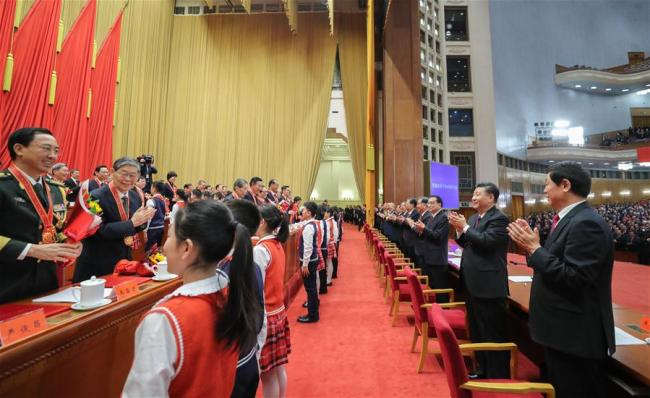 Chinese President Xi Jinping, also general secretary of the Communist Party of China (CPC) Central Committee and chairman of the Central Military Commission, and other Chinese leaders applaud for the personnel awarded for their outstanding contributions to the reform and opening-up during a grand gathering to celebrate the 40th anniversary of China's reform and opening-up at the Great Hall of the People in Beijing, capital of China, Dec. 18, 2018. Xi made an important speech at the gathering. [Photo: Xinhua/Ju Peng]