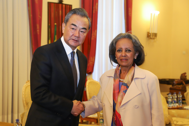 China's Foreign Minister Wang Yi (L) and Ethiopia's President Sahle-Work Zewde (R) shake hands ahead of a meeting at the national palace in Addis Ababa, on January 3, 2019 during Wang's official four-nation Africa tour. [AFP/Michael Tewelde]