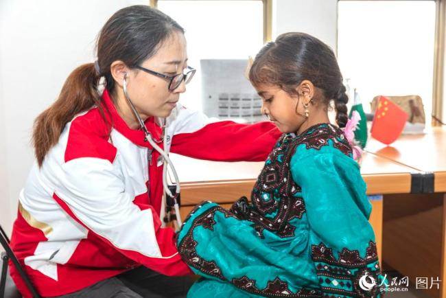 A doctor from the China Medical Team examines a girl at Gwadar Port in southwest Pakistan. [Photo: people.cn]