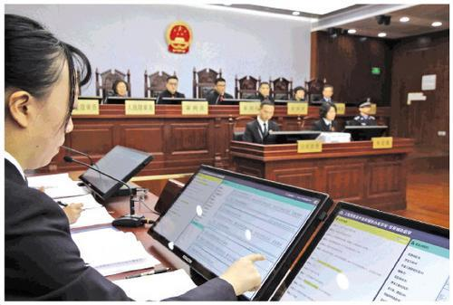 A public prosecutor reviews evidence presented by the AI system during a hearing at a Shanghai court on Wednesday, January 23, 2019. [Photo: Legal Daily]