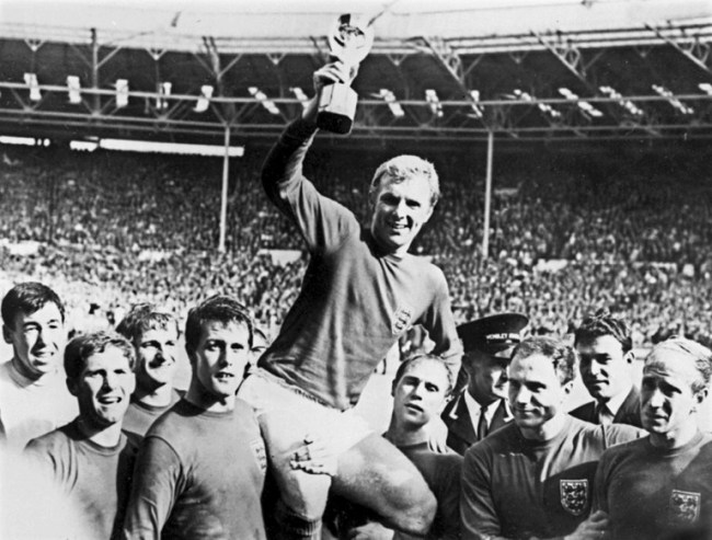 In this file photo taken on July 30, 1966 England's national soccer team captain Bobby Moore (C) holds aloft the Jules Rimet World Cup trophy as he is carried by his teammates including (from L) Gordon Banks, Alan Ball, Roger Hunt, Geoff Hurst, Ray Wilson, George Cohen and Bobby Charlton, following England's victory over Germany (4-2 in extra time) in the World Cup final 30 July 1966 at Wembley stadium in London. [Photo: AFP]