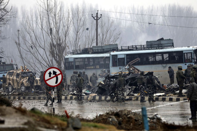 Indian paramilitary soldiers stand by the wreckage of a bus after an explosion in Pampore, Indian-controlled Kashmir, Feb. 14, 2019. [Photo: AP/Umer Asif]