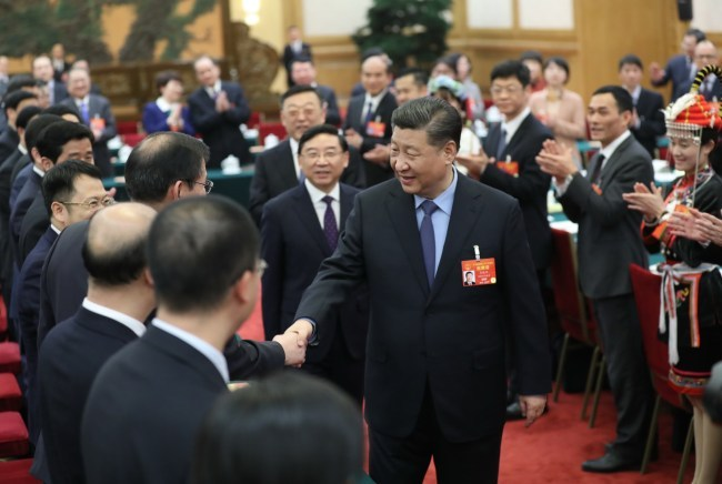President Xi Jinping shakes hands with his fellow deputies from Fujian Province at the second session of the 13th National People's Congress in Beijing on March 10, 2019. [Photo: Xinhua]