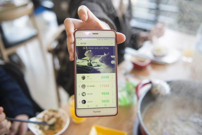 A student at Zhejiang Gongshang University presents the number of daily steps recorded in WeChat at an on-campus restaurant to get a discount on their bill on Wednesday, March 13, 2019. [Photo: IC]