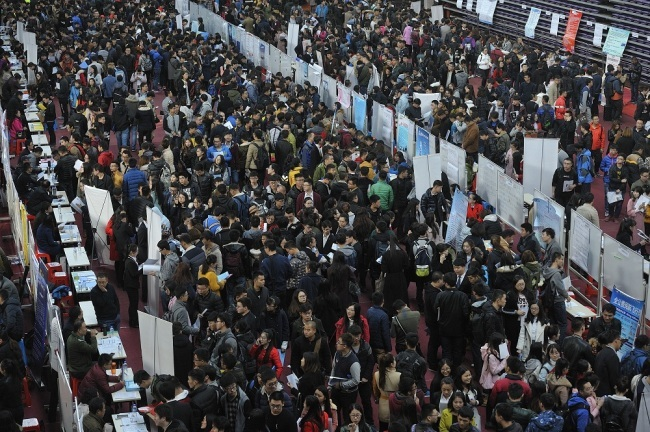 Chinese graduates and students are interviewed at booths of recruiters during a job fair at a university in Harbin city, Heilongjiang province, 20 October 2016. [File Photo: IC]