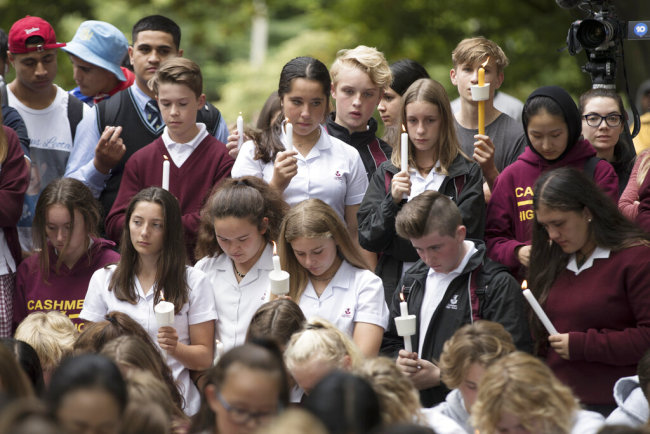 Students hold candles during a moment of silence as they gather for a vigil to commemorate victims of Friday's shooting, outside the Al Noor mosque in Christchurch, New Zealand, Monday, March 18, 2019. [Photo: AP]