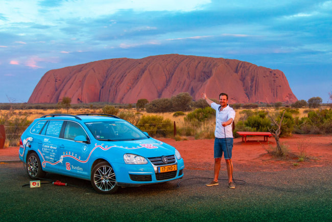 "This handout photo taken on December 31, 2018 and released on April 7, 2019 from Dutch driver Wiebe Wakker (C-R) shows him at Uluru in the Northern Territory with his retrofitted station wagon nicknamed ""The Blue Bandit"" during his round-the-world trip in the electric car. [Photo: PLUG ME IN PROJECT/Wiebe Wakke/AFP]"