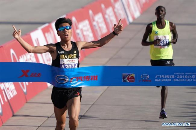 Liu Hongliang (left) was the first across the finish line for the 2019 Beijing Half Marathon on Sunday, April 14, 2019. [Photo: Xinhua/Ju Huanzong]
