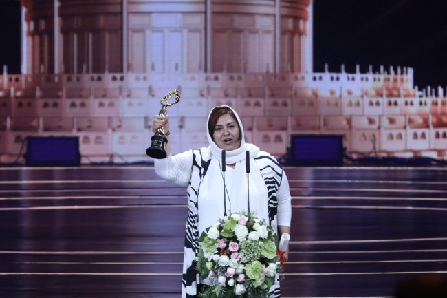 """Forough Ghajabagli raises the trophy after winning the Best Actress award for her role in """"Tehran: City of Love"""" at the closing ceremony for the 9th Beijing International Film Festival, on April 20, 2019, in Beijing. [Photo: IC]"""