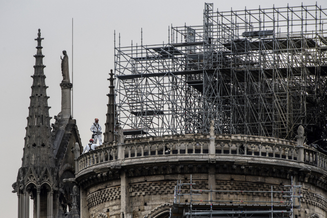 Workers stand on the roof of the Notre-Dame de Paris cathedral in Paris on April 23, 2019, one week after a fire devastated the cathedral. [Photo: AFP]