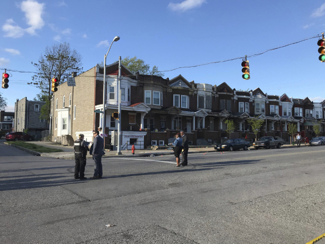 Authorities stand at Edmondson and Whitmore after multiple people were shot, Sunday, April 28, 2019, in Baltimore. [Photo: AP]