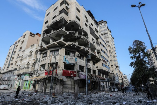 A damage building stands on a debris-strewn street in Gaza City on May 5, 2019, that was hit during Israeli air strikes on the Palestinian enclave. [Photo: AFP/Mahmud Hams]