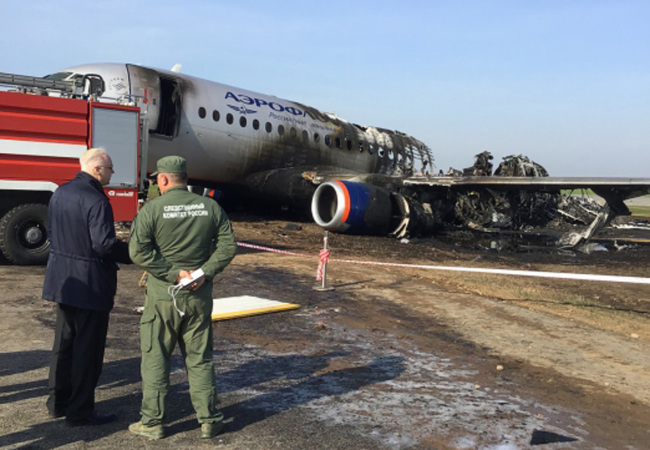This handout picture taken and realeased on May 6, 2019 shows a head of Russian Investigative Committee Alexander Bastrykin (L) as he speaks with unidentified investigator at a site of a fire of a Russian-made Superjet-100 at Sheremetyevo airport outside Moscow. [Photo: AFP]