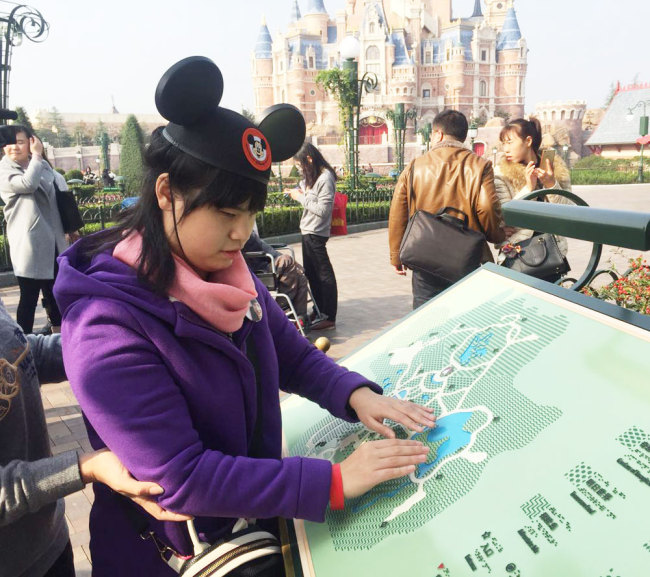 A visually impaired woman uses a braille map at Shanghai Disney Resort. [File photo: Shanghai Observer]