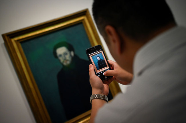 """This picture taken on June 14, 2019 shows a man using his mobile phone to take a picture of an oil canvas entitled """"Self Portrait"""" by Pablo Picasso during an exhibition """"Picasso Birth of a Genius"""" at an art gallery in Beijing. [Photo: AFP/Wang Zhao]"""