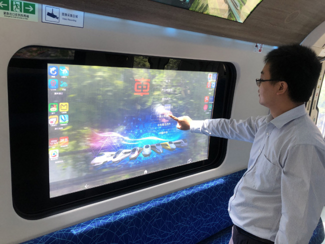 A staff member displays how to use the touch screen on the window of the carriage. [Photo: IC]