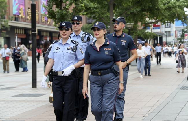 Italian and Chinese police officers walk through the crowd as they carry out a joint patrol on Wangfujing Street in downtown Beijing on June 24, 2019. [Photo: VCG]